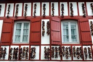 piment d'Espelette AOP suspendus à la façade d'une maison basque typique à l'automne